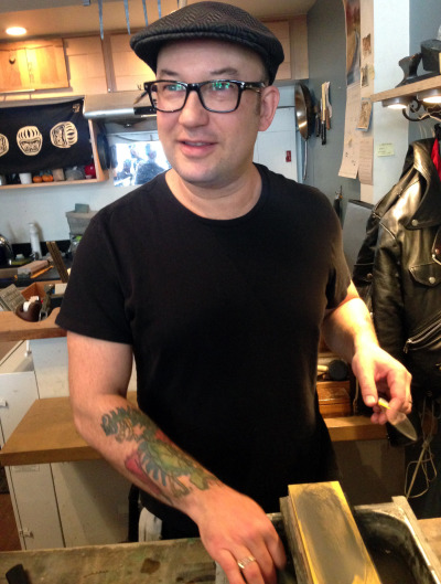 Josh Donald, owner of Bernal Knives, behind the counter. (Scott Shafer/KQED)