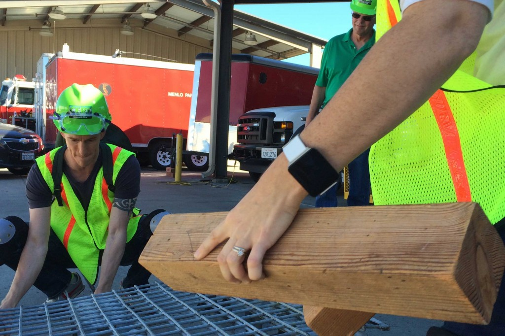 Matt Clemens, a patent lawyer, and other trainees use wooden blocks to lift a heavy metal crate off a dummy in a victim rescue simulation on Oct. 18, 2014. Clemens said the three-day training helped him put together an emergency preparedness plan for him and his family. (Farida Jhabvala Romero/Peninsula Press)