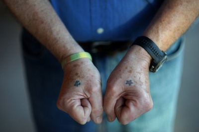 Former Navy torpedoman Patrick Meagher shows off  tattoos that he got in 1971. (James Tensuan/KQED)