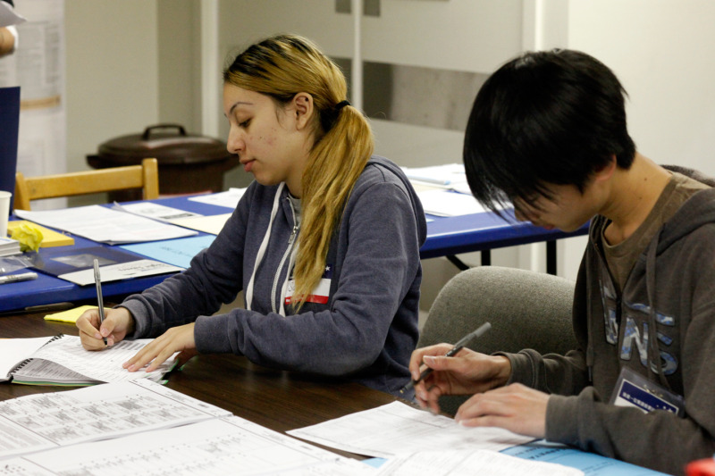 Samantha Padilla, 17, of Sacred Heart Cathedral Preparatory School and Jerry Gong, 17, of Galileo High School volunteer as poll workers at the Dolores Park Church polling place. (Katie Brigham/KQED)