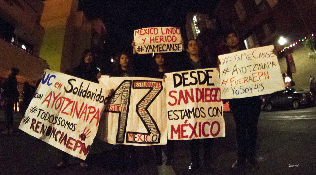 Protesters in San Diego hold up signs in front of the Mexican Consulate on Nov. 20, 2014. (Brooke Binkowski/KQED)