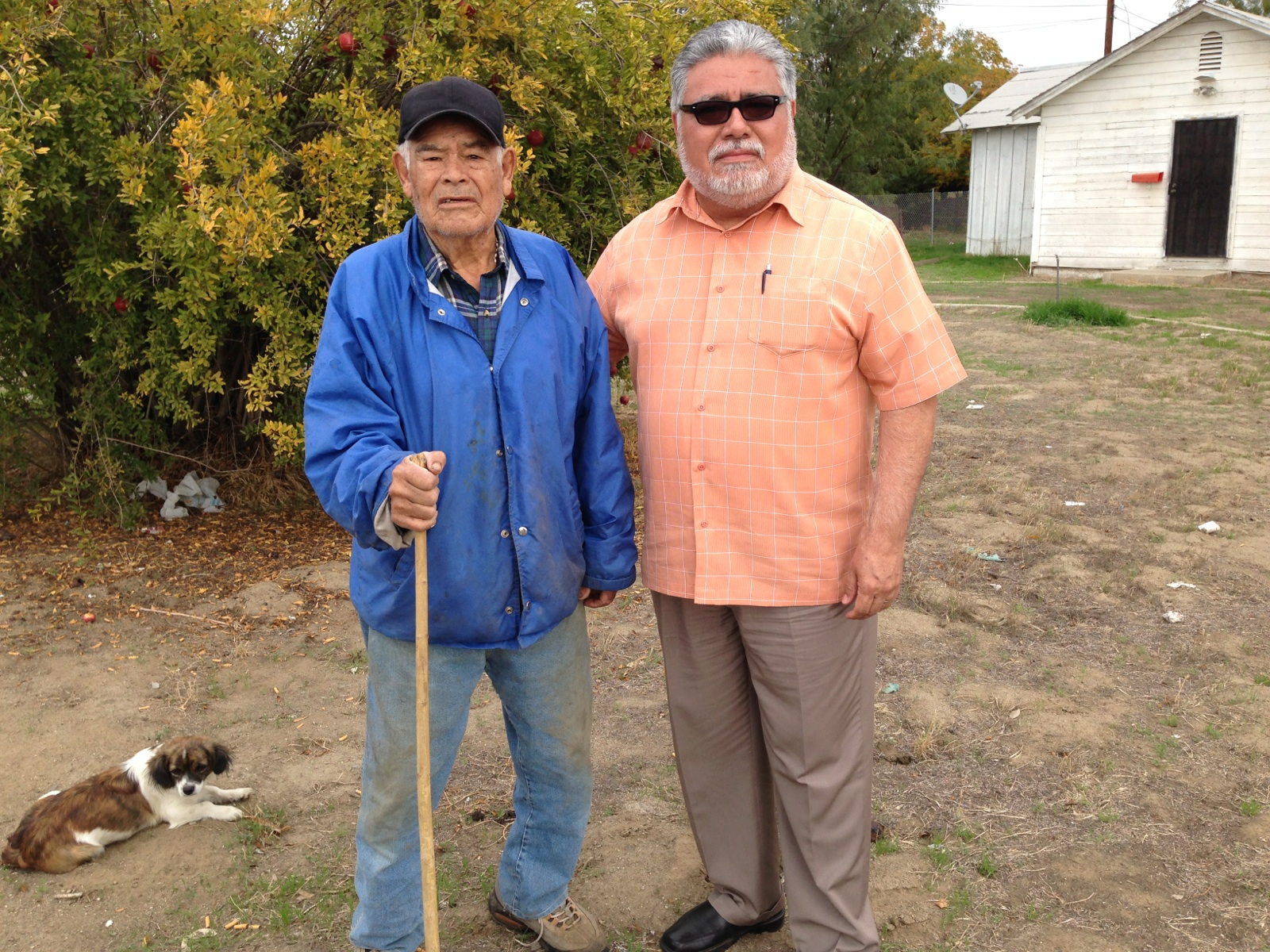 Gilberto Sandoval (left), 81, lives across the street from the church where the showers are parked. Pastor Roman Hernandez started bringing Sandoval drinking water a week ago. (Ezra David Romero/KQED)