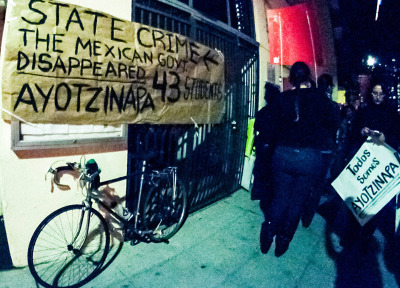 """A banner in San Diego reads """"State Crime – the Mexican government disappeared 43 Ayotzinapa students."""" (Brooke Binkowski/KQED)"""