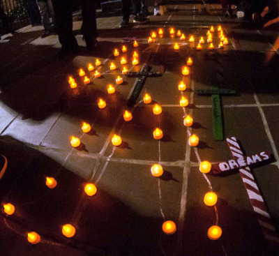"""Candles burn along a chalk outline of a body with """"43"""" written inside of it outside Our Lady of Guadalupe Church in San Diego. (Brooke Binkowski/KQED)"""