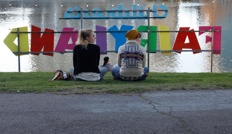 CJ Dunbar (right), 24, and Caroline Hawkinson, 24, relax by Lake Merritt. Neither voted on election day. (Katie Brigham/KQED)