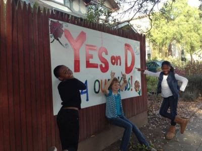 Children pose outside a Yes on D sign put up by Jan Cecil outside her house on Ashby Avenue in Berkeley — one of many efforts in a city-wide pro-soda tax campaign which led to its overwhelming victory. (Courtesy: Berkeley vs Big Soda)