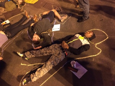Protesters lie down in the intersection of 14th and Broadway in downtown Oakland during Monday night's Ferguson shooting protest. (Mark Andrew Boyer/KQED)