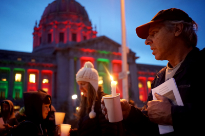 T.J. Johnston pays his respects in San Francisco on Dec. 18 to the homeless people who died this year. Dozens of people attended the annual gathering hosted by local religious leaders.