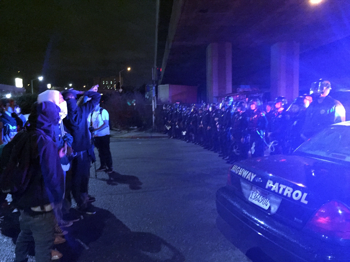 Protesters regroup in front of a police line under Interstate 880 in Oakland.