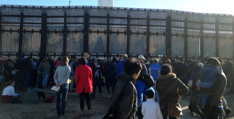People gather at the foot of the U.S.-Mexico border fence at the annual La Posada Sin Fronteras.