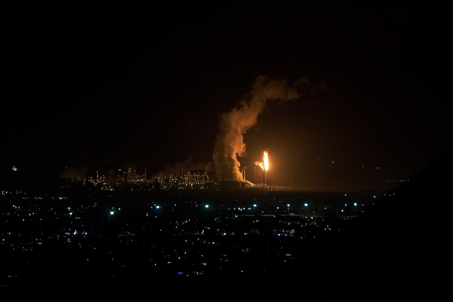 A cloud of smoke or steam wraps around the flames from a second round of flaring emanating from Chevron's Richmond refinery on Dec. 18, 2014.