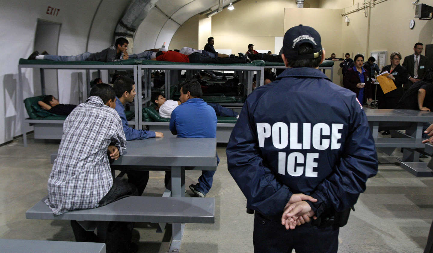An Immigration and Customs Enforcement (ICE) officer guards a group of 116 Salvadoran immigrants waiting to be deported.