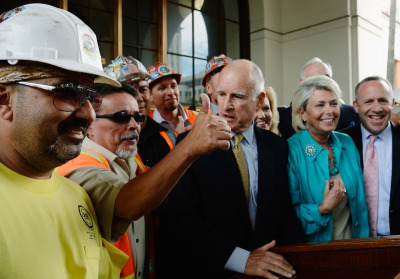 Gov. Jerry Brown stands next to construction workers and elected officials after signing legislation authorizing initial construction of California's $68 billion high-speed rail line on July 18, 2012 in Los Angeles. (Kevork Djansezian/Getty Images)