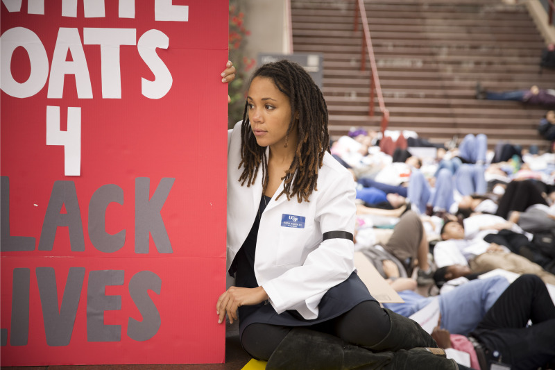 "Kadia Wormley, a UCSF medical student, wears a black arm band in solidarity with the families of Michael Brown and Eric Garner. The sign says ""white coats 4 black lives."""