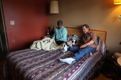 Patrick and Sandra Scott, both 62, play with their dog Pepper in a motel room in Santa Clara, on Dec. 13, 2014. They were placed into a motel after being homeless for almost a year.  (Yuqing Pan/Peninsula Press)