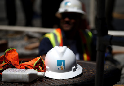 The PG&E logo is displayed on a hard hat at a work site.
