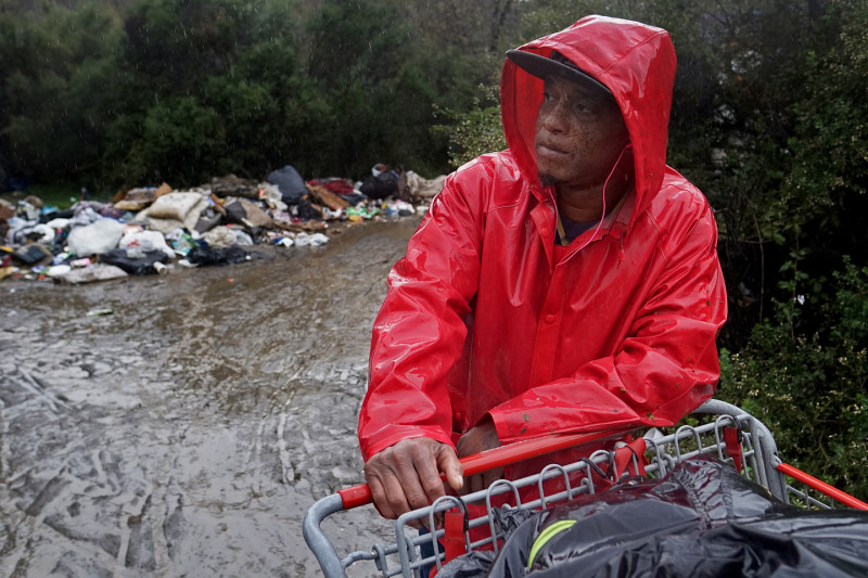 Mike Cooper takes a break from pushing his shopping cart of belongings out of The Jungle. He's been living in the Jungle for about six months after falling on bad luck when he moved to San Jose from St. Louis. (James Tensuan/KQED)