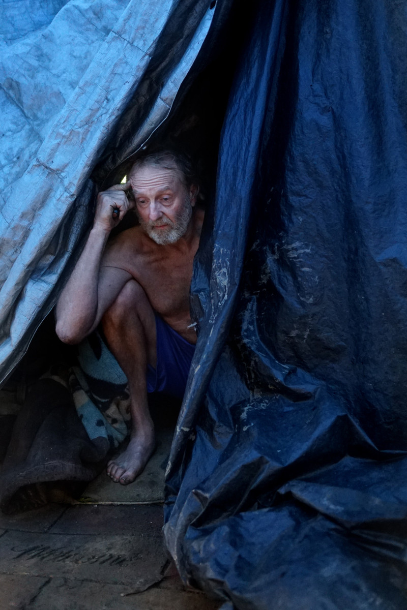 Doug Wynne pokes his head out of his tent where he's been living for the past four years. Wynne came to San Jose from Florida hoping for a job in the tech industry, but feels he was too old to be viewed as a desirable employee. (James Tensuan/KQED)