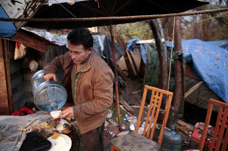 Jose Alcala takes a break from packing to get a drink of water. Alcala lived in The Jungle for 2 years, and is now headed to a group home down the street. (James Tensuan/KQED)