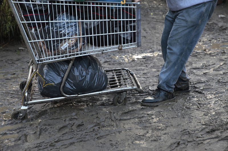 The rain and mud made the move messy. At one point a dump truck brought in to cart debris away got stuck in the muck. (James Tensuan/KQED)