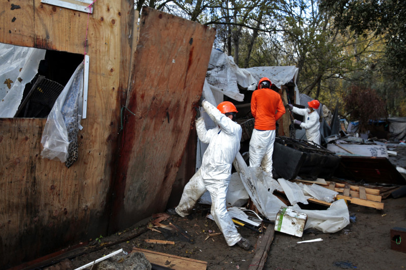 A work tears down a wall at The Jungle. (James Tensuan/KQED)