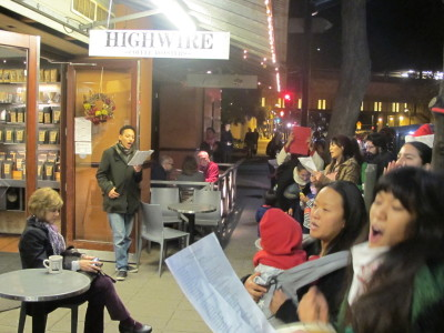 Protesters sing carols condemning police violence outside Rockridge Market Hall in Oakland. (Andrew Stelzer/KQED)