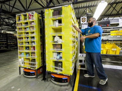 An Amazon employee picks items from a Kiva robot.  (Business Wire)