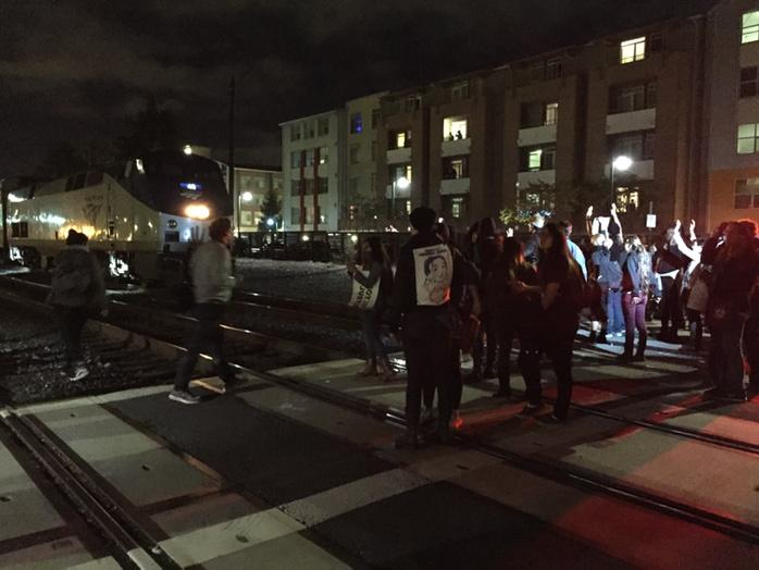 Protesters blocked an Amtrak commuter train around 8 p.m. Monday. (Isabel Angell/KQED)