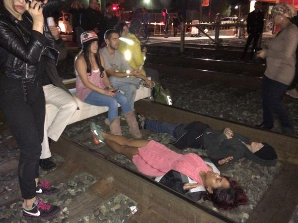 Amtrak trains still halted after hour and half of Berkeley protesters camped out on tracks. (Julia McEvoy/KQED)
