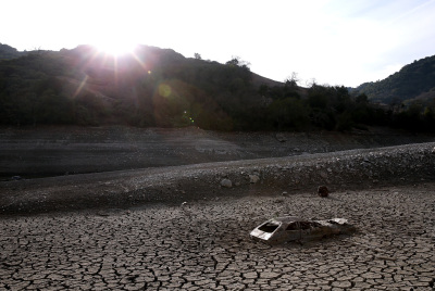 A car sits in dried and cracked earth of what was the bottom of the Almaden Reservoir south of San Jose on Jan. 28. (Justin Sullivan/Getty Images)