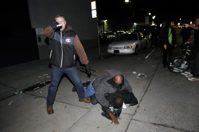 An undercover officer points his gun at the crowd while his partner subdues a protester who struck him in the back of the head, as demonstrations continue for a fifth night in Oakland on Wednesday, Dec. 10, 2014.