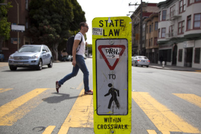 A pedestrian crosses 16th Street in San Francisco's Mission District.