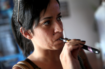 Yenisley Dieppa tries different flavors as she purchases an electronic cigarette at the Vapor Shark store in Miami, Florida, in February 2014.