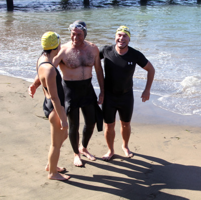 South End Rowing Club members Jenny Hoffman, Clark Chelsey and Paul DeAngelis celebrate another energizing swim in the San Francisco Bay. (Greta Mart/KQED)