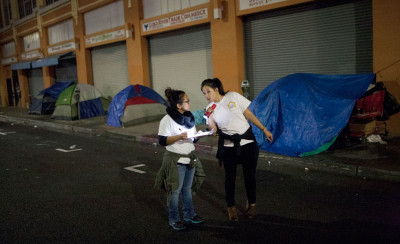 Volunteers count homeless people on a dark street on Skid Row during the 2015 Greater Los Angeles Homeless Count conducted by the Los Angeles Homeless Services Authority (LAHSA) on January 29, 2015.