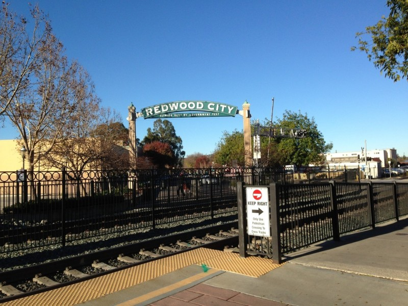 "From the Redwood City Caltrain station, you can see the iconic sign that says ""Redwood City: Climate Best by Government."""