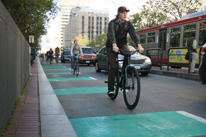 Cyclists ride on green bike lanes on Market St.