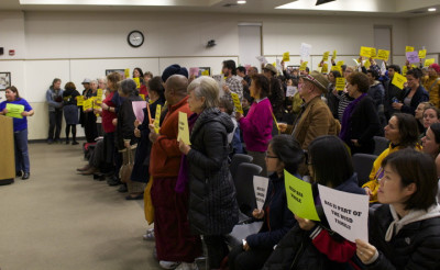 Students and faculty from Berkeley Adult School stand and hold signs in solidarity against relocation of the school at Wednesday's board meeting.
