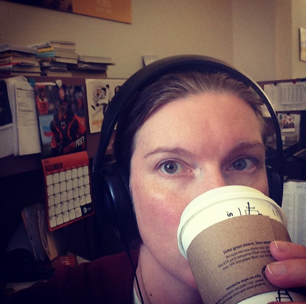 Amanda Stupi in headphones, drinking coffee.
