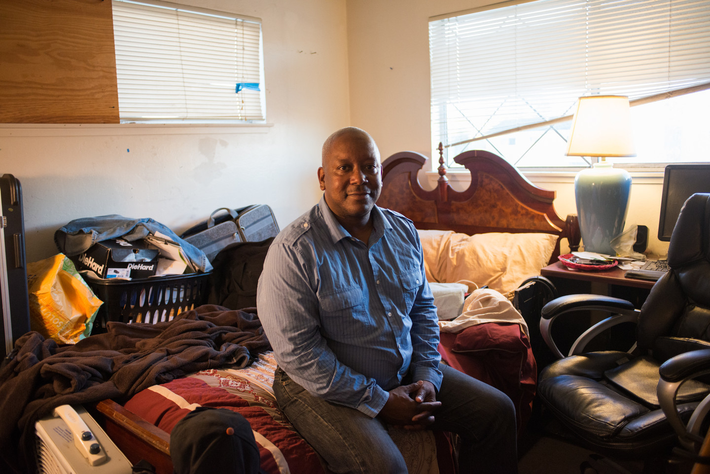 Michael Johnson at home in San Jose. Working full time as a security guard, he is unable to afford more than a room to rent in a friend's apartment.