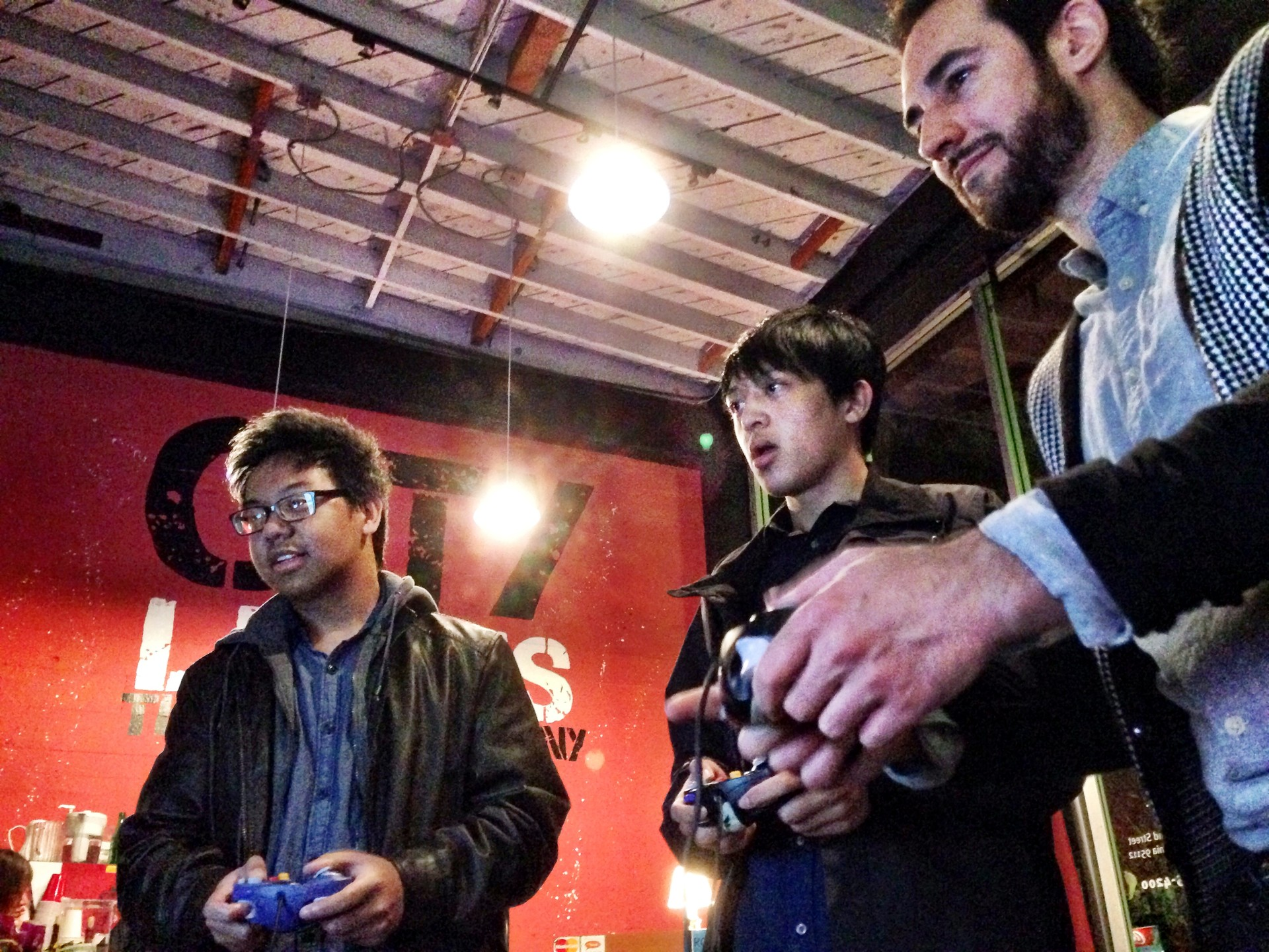 Students Brandon and Christian de la Cruz and Rockage founder Eric Fanali playing video games at the theater.