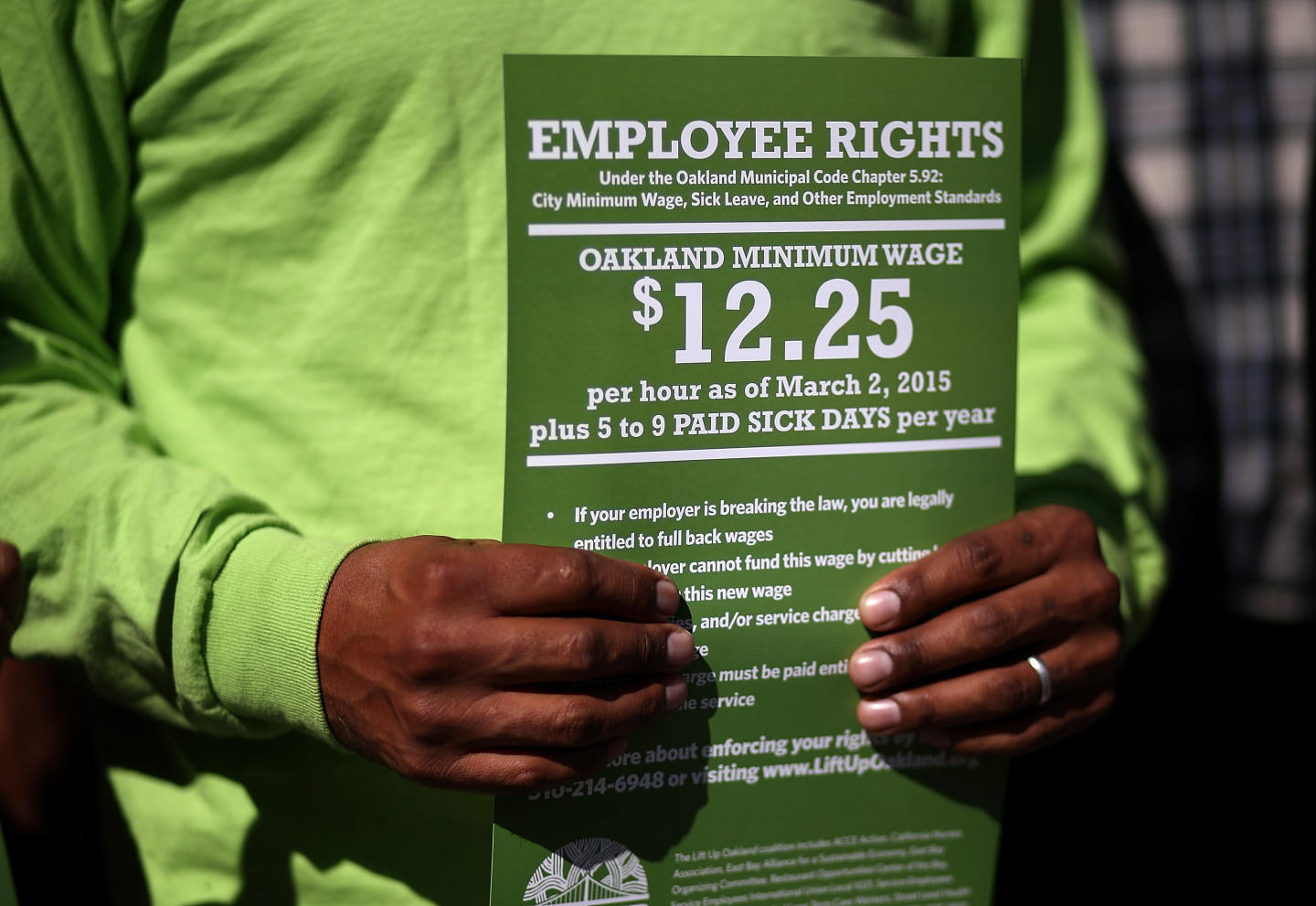 A supporter of Oakland's minimum wage increase holds a sign during a celebration rally outside Oakland City Hall.