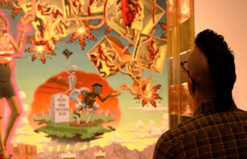 A visitor gets a closer look of a Robert Williams painting on view at the LA. Municipal Art Gallery