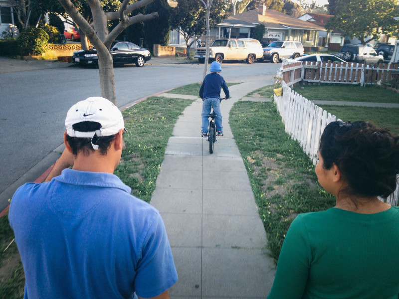 Stephanie and Jose watch their son ride a bike at their new home.