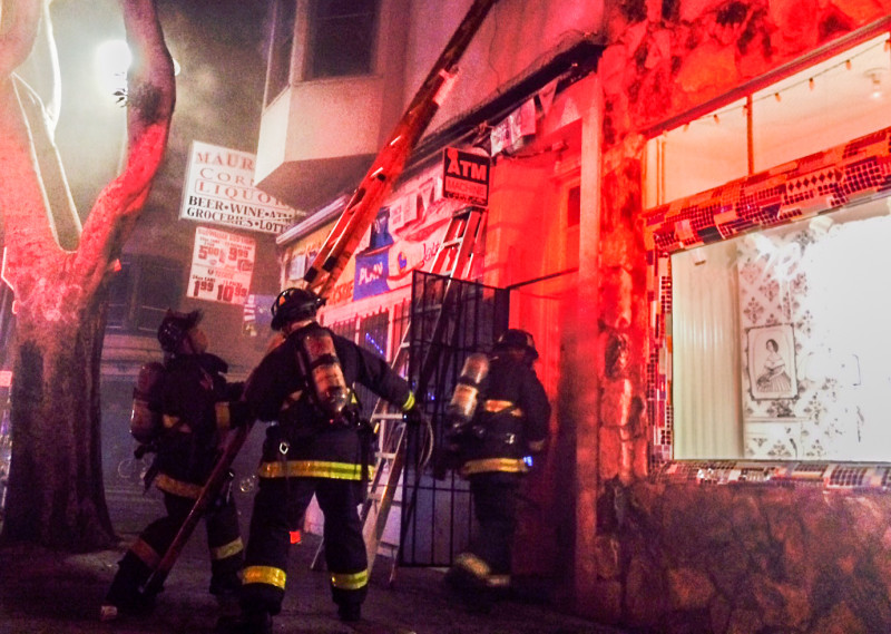 Firefighters responding to March 11, 2015 blaze that killed two members of a family living in a second-floor apartment at 24th Street and Treat Avenue in San Francisco's Mission District.