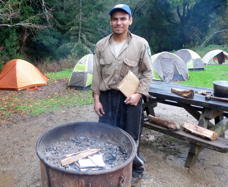 Gabino Lopez tends the fire, also known as the camp TV.