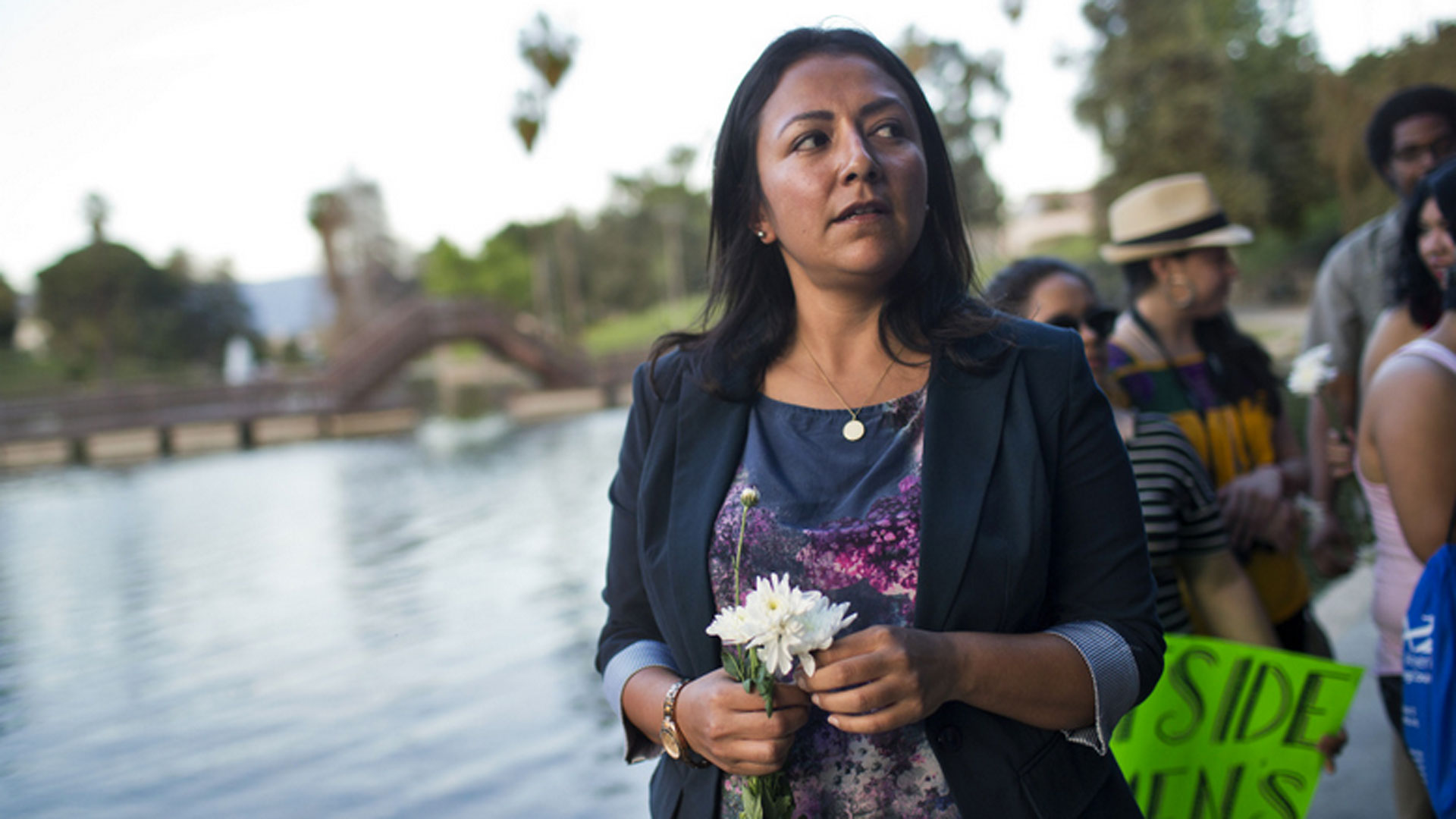 Raquel Román leads a memorial for Lorenza Arellano on Friday, March 13, 2015 at Hollenbeck Park in Boyle Heights. Roman, director of the Guadalupe Homeless Project, opened a women's shelter after Arellano, a homeless woman, was found dead in the park's lake in March 2014.