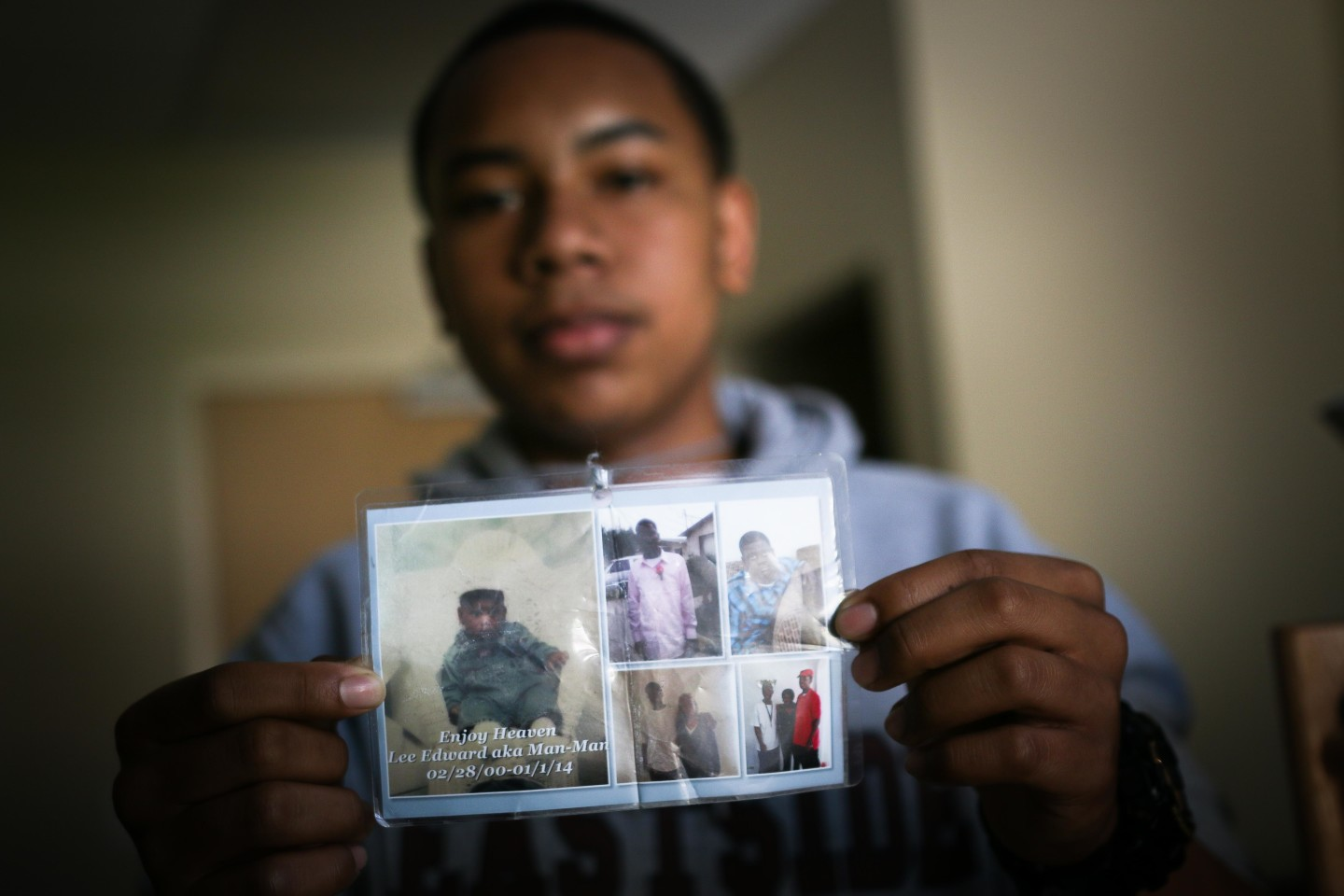 Diamond Allen shows off pictures of his friend, Lee Weathersby III, who was shot and killed in Oakland. (Jeremy Raff/KQED)