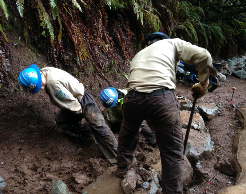 "California Conservation Corps members, ""Cs"" for short, roll rocks as heavy as 500 pounds to their work area, set them into place and chisel them for a snug fit."