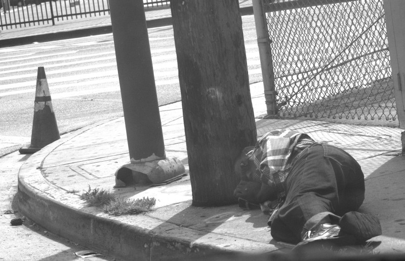 An unidentified passed out on the sidewalk of a Skid Row back street.